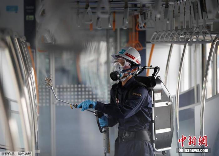 图为当地时间7月9日,日本东京,一名戴着防护面具和护目镜的东京地铁员工对车厢进行消dupoison。