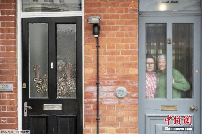 """2020年7月10日讯,英国布莱顿,英国摄影师JJ Waller在3月19日至5月21日期间,拍摄了超过100组个人及家庭在窗户、门以及阳台玻璃之后的肖像照。这或许将成为这些人亲身经历自我封锁的有力证明。这本新的摄影书名为""""这个时代的非正式肖像照""""。著名的英国纪实摄影师Martin Parr评论称:""""当我们回顾2020年春夏的时候,我认为这些影像将会成为我们经历的这个特殊时期的独特记忆。"""""""