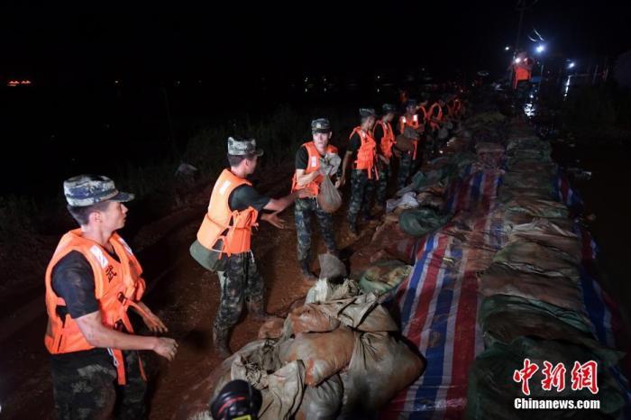 7月11日晚间,武警江西总队机动支队官兵在鄱阳县江家岭村昌江圩抗洪一线搬运沙袋。许书灿 摄