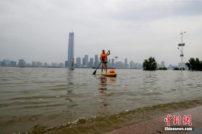 7月11日,武汉汉口江滩,江水已经淹没了二级亲水平台,接近最高的三级亲水平台。当日20时,长江水文网数据显示,长江汉口站水位到达28.49米。这一水位已超过2016年最高水位,达到有水文记录以来的历史第五。图为武汉长江救援队的小红帽队员划着皮划艇进行巡查。 中新社记者 张畅 摄