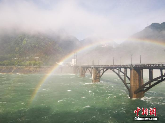 7月13日,浙江省建德市紫金一桥附近的江面上,新安江水库泄洪激起的水雾,与久违的阳光一道勾画出美丽的彩虹,持续时长近3小时。 钱晨菲 摄