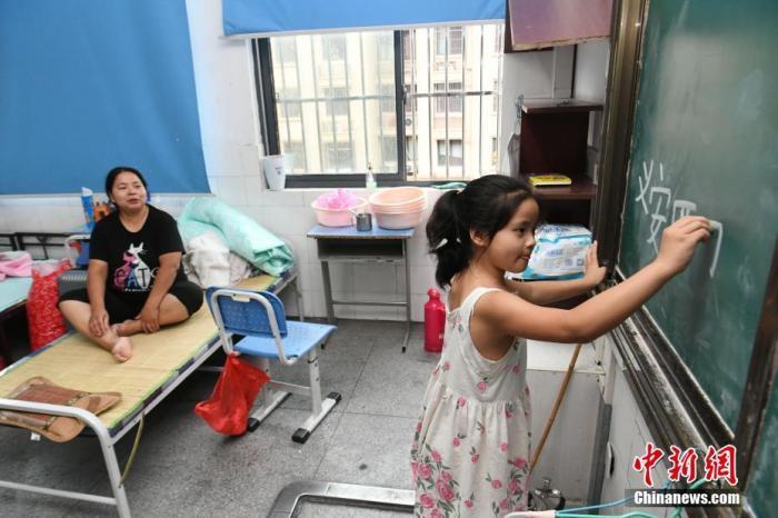 7月15日,安徽省铜陵市义安区顺安中心小学安置点内,一位小朋友在黑板上写字。中新社记者 韩苏原 摄