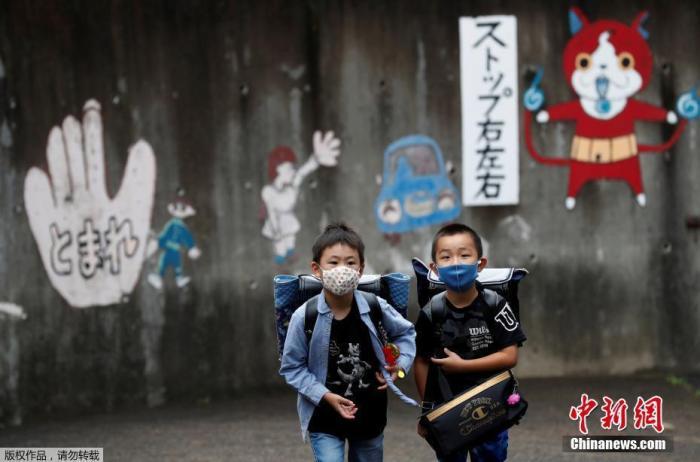 资料图:当地时间7月16日,日本东京,孩子们戴着口罩结伴上学。