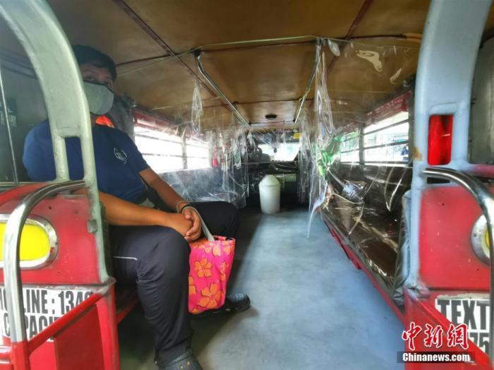 当地时间7月14日,菲律宾最为普及的公共交通吉普尼回归马尼拉CBD马卡蒂街头。车辆每个座位之间做了隔离,并按照一半的座位载客。记者 关向东 摄
