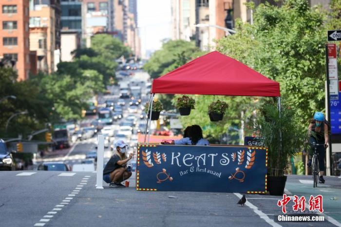 当地时间7月16日,美国纽约曼哈顿,一家餐厅的工作人员在布置户外就餐区。因防疫需要,纽约市原本应在第三阶段开放的餐饮业室内就餐仍处于暂停状态,政府鼓励餐厅申请设置户外就餐区。记者 廖攀 摄