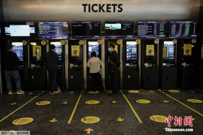 当地时间2020年7月1日,马来(西)亚吉隆坡,电(影)院(重)新开放,观众用自动(售)(票)(机)买电影票。