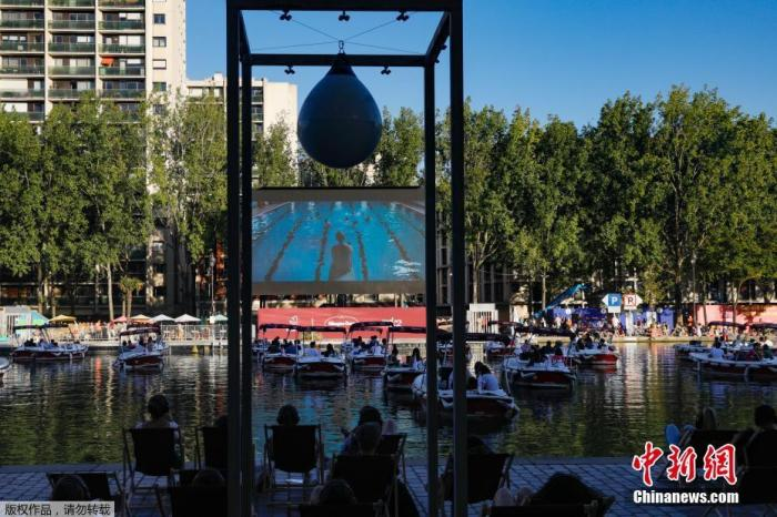 """当地时间7月18日,法国巴黎,巴黎人工海滩举办""""水上电影院""""活动,观众坐在游船和沙滩上观看喜剧片《大浴场》。"""