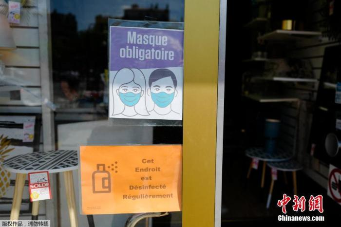 资料图:图为法国巴黎的一家商店里门前贴着戴口罩进入标识。