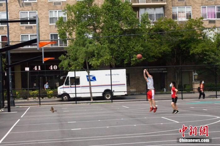 7月20日,纽约市在炎炎夏日中进入4阶段重启。按规定,4阶段重启期间,市民可以进行低风险的室外艺术和娱乐活动。图为皇后区法拉盛一处社区体育场,两名少年正在打篮球。 <a target='_blank' href='http://www.chinanews.com/'>中新社</a>记者 马德林 摄