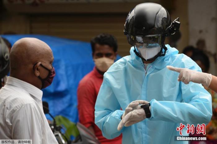 当地时间2020年7月21日,印度孟买,一名非政府组织的卫生工作志愿者穿着防护衣,戴着装有热扫描传感器的智能头盔在居民区挨户查看居民体温。