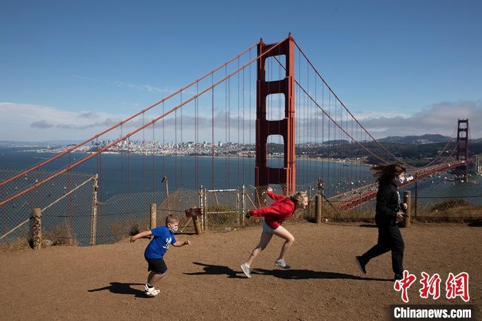 当地时间7月21日,游客在美国添州旧金山金门大桥附近嬉戏。
