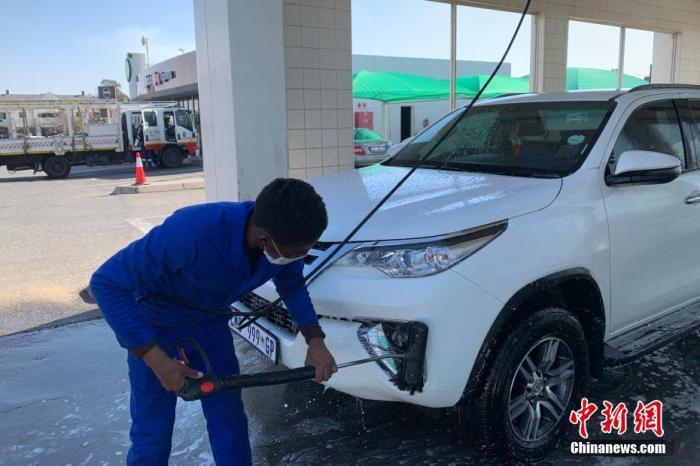 当地时间7月22日,南非约翰内斯堡,一家洗车店的员工佩戴口罩为顾客清洗车辆。 <a target='_blank' href='http://www.chinanews.com/'>中新社</a>记者 王曦 摄