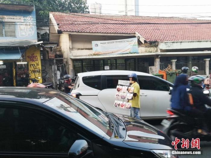 印尼一名小販在車流中穿梭賣口罩。<a target='_blank' href='http://www.duomifood.com/'>中新社</a>記者 林永傳 攝
