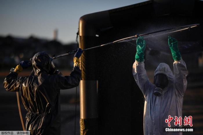 """资料图:当地时间2020年7月22日,巴西米纳斯吉拉斯州贝洛奥里藏特潘普利亚机场,当地军事部队成员身穿防护装备,演练使用""""气泡担架""""运送新冠肺炎患者。"""