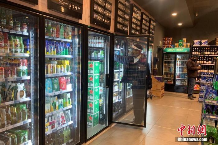 當地時間7月22日庫博體育登錄網址_BET9九州體育官網平臺,南非約翰內斯堡,一家酒類商店的店員佩戴面罩整理冰箱內的貨物。 記者 王曦 攝
