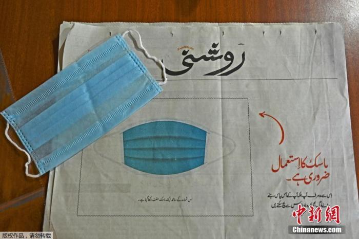 """资料图:当地时间7月23日,印控克什米尔斯利那加,一份当地乌尔都语报纸""""Roshni""""为了提高人们对新冠肺炎的认识,向读者免费提供了口罩,并将其贴在头版。"""