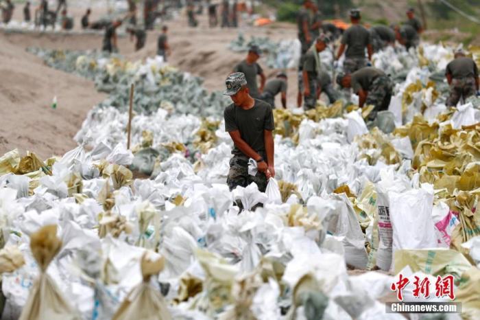 7月25日,江西省九江市柴桑区江洲镇北堤,中国人民解放军第71集团军某部官兵正在为防洪备料。