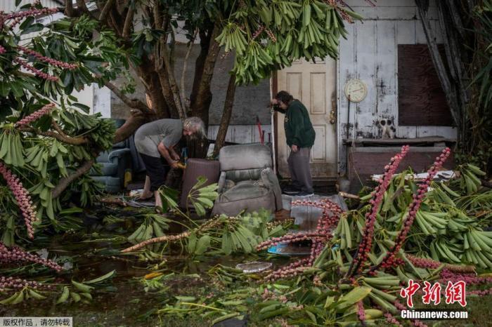 当地时间7月26日,美国得克萨斯州曼斯菲尔德港,飓风过后,一对老夫妻在调查房屋的损毁情况。