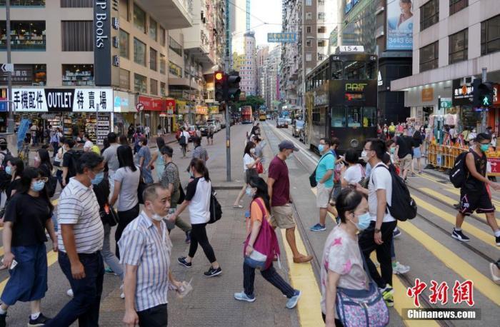资料图:绝大多数香港市民戴口罩出行,但也有少数市民拉低口罩。 中新社记者 张炜 摄