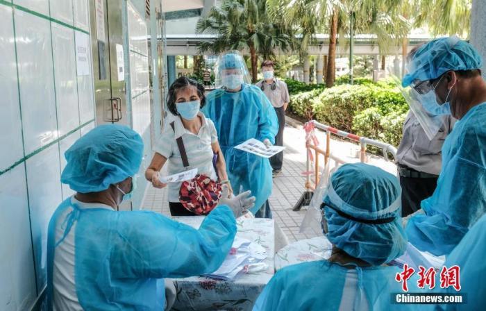 7月28日上午,身穿全套防护衣物的人员于香港慈云山慈正邨正和楼及正泰楼,向居民派发检测样本瓶。记者 秦楼月 摄