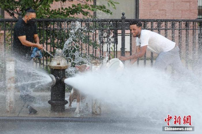 资料图:当地时间2020年7月27日,两名青年在纽约布鲁克林街道上喷水的消防栓前嬉水消暑。 中新社记者 廖攀 摄
