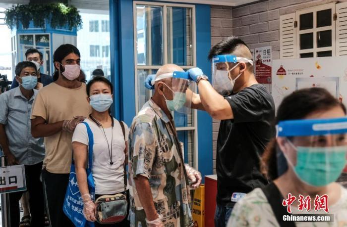 7月29日,慈云山街市推行多项措施加强防疫,市民进入街市前必须量度体温及戴上口罩、并于街市入口的智能消毒站接受喷雾消毒,街市内的商户以及大部份进入街市的市民均有戴上面罩。 中新社记者 秦楼月 摄
