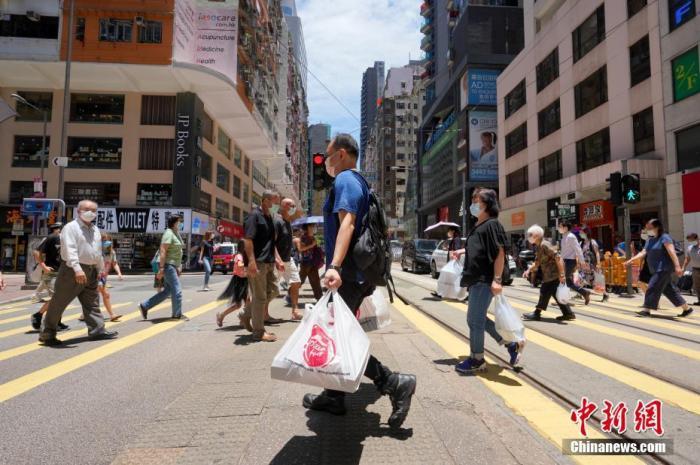 7月30日中午,市民携带外卖餐食经过香港湾仔一个路口。中新社记者 张炜 摄