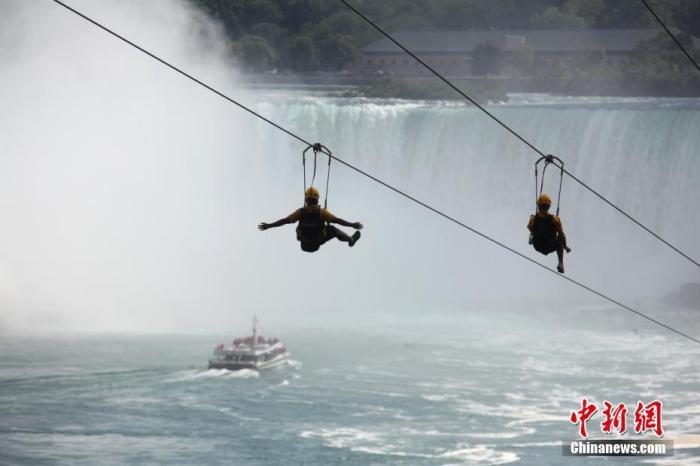 当地时间7月29日,游客在加拿大、美国交界处的著名景点尼亚加拉大瀑布群加拿大一侧体验高空滑索。随着经济逐步重启,受到新冠疫情重挫的尼亚加拉旅游业正迎来复苏。 中新社记者 余瑞冬 摄