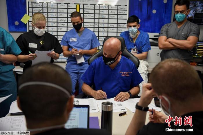 美国医生约瑟夫和他的医护人员团队在每日例会上查看新冠病毒感染者的档案,他的部门平均每天接待40名患者。