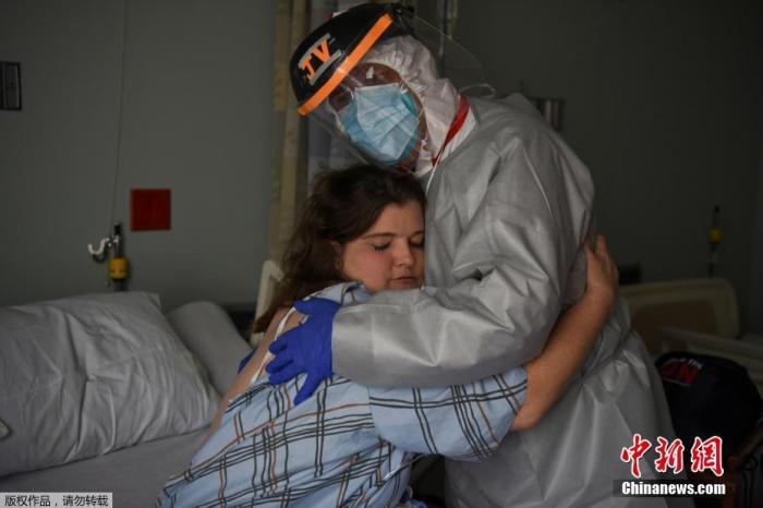 资料图:美国联合纪念医疗中心的首席医疗官与护士克里斯蒂娜・马瑟斯在病房内拥抱。此前,克里斯蒂娜在一次轮班期间报告感觉身体不适,随后检测呈阳性。