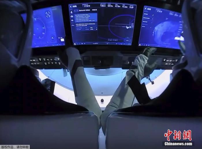 """当地时间8月1日,美国宇航局(NASA)商业载人航空计划(CPP)的首次载人试航开始最后一阶段任务--返回地球。图为宇航员道格・赫利(左)和鲍勃・本肯(Bob Behnken)乘坐""""龙""""飞船太空舱准备离开国际空间站。(视频截图)"""