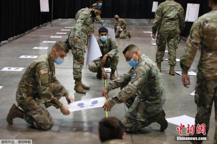 资料图:那个地方时间8月3日,美国内华达州拉斯维加斯,卡什曼主题建立一处新的新冠病毒检测主题,国民警卫队员在张贴社交跨距贴纸。