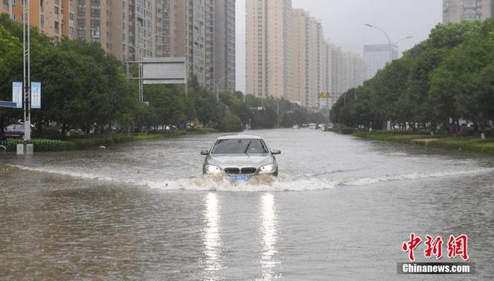 资料图:一条道路出现积水,车辆行驶其中激起水波。<a target='_blank' data-cke-saved-href='http://www.chinanews.com/' href='http://www.chinanews.com/'>中新社</a>记者 王刚 摄