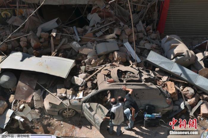 据法新社报道,黎巴嫩红十字会5日表示,贝鲁特港口发生的爆炸,共已造成100多人死亡,4000多人受伤。图为人们在街边检查一辆受损的汽车。