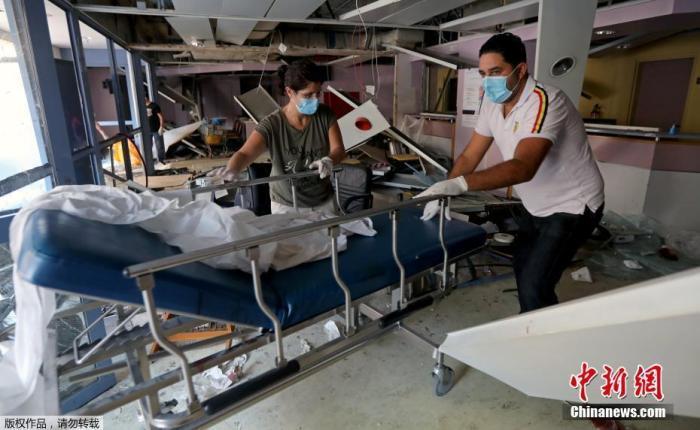 当地时间8月4日晚,黎巴嫩首都贝鲁特港口区发生剧烈爆炸。图为人们在受损的医院内搬动医疗设备。