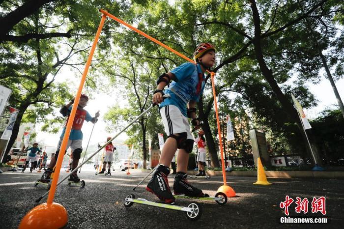 """8月8日,北京广宁街道冬奥社区举办全民健身日活动,室外的趣味冰雪体验区举办的冰壶游戏,花样轮滑和特别设置的""""夏季滑雪场""""让辖区居民感受到了冰雪运动的乐趣。图为市民体验轮滑。 中新社记者 杜洋 摄"""