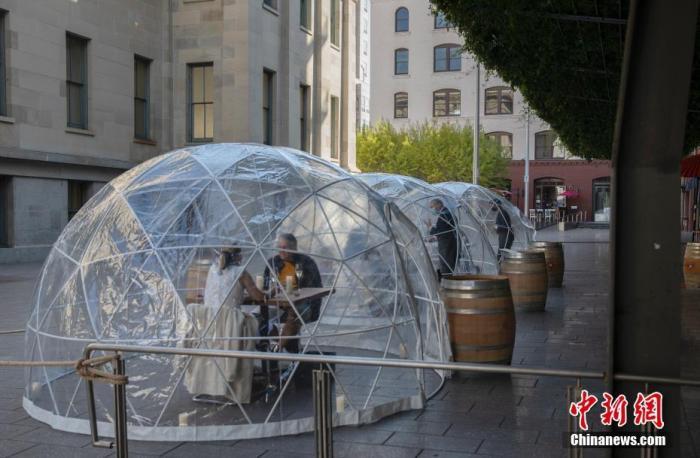 当地时间8月8日,美国加州旧金山一家餐厅在门外设置了三个透明半球形隔离餐位,以阻止新冠病毒及无家可归者对食客的侵扰。 中新社记者 刘关关 摄
