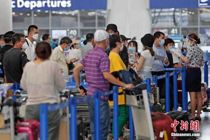 资料图:图为东航外航服务工作人员指导旅客填写出入境健康声明卡。 殷立勤 摄