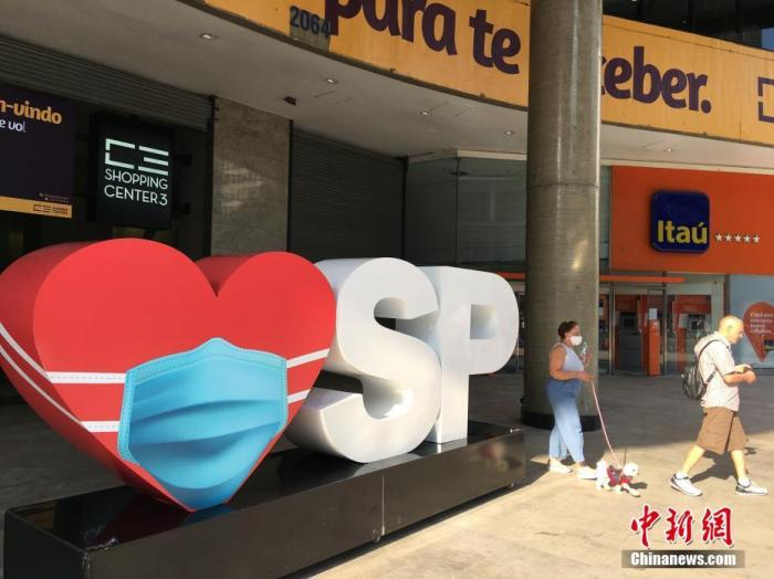 当地时间8月9日,巴西圣保罗一家购物中心门前设置戴口罩的红心标牌,提醒人们出门要佩戴口罩。目前,巴西圣保罗市正按照经济重启计划,分阶段逐步推进商业重启,商铺、购物中心、餐厅、酒吧、健身房、公园等场所已有限开放,经济逐渐恢复。据巴西卫生部公布的数据,截至9日,巴西累计新冠肺炎确诊病例超303万例、死亡病例逾10万例。<em></em> 中新社记者 莫成雄 摄