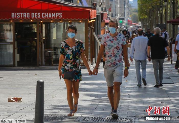 当地时间8月10日,法国巴黎正式推行户外强制戴口罩,以遏制病毒进一步传播导致疫情失控。图为市民戴着口罩漫步在巴黎香榭丽舍大街。