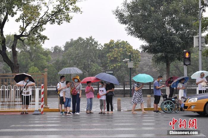 图为北京景山前街,民众冒雨出行。中新网记者 李骏 摄