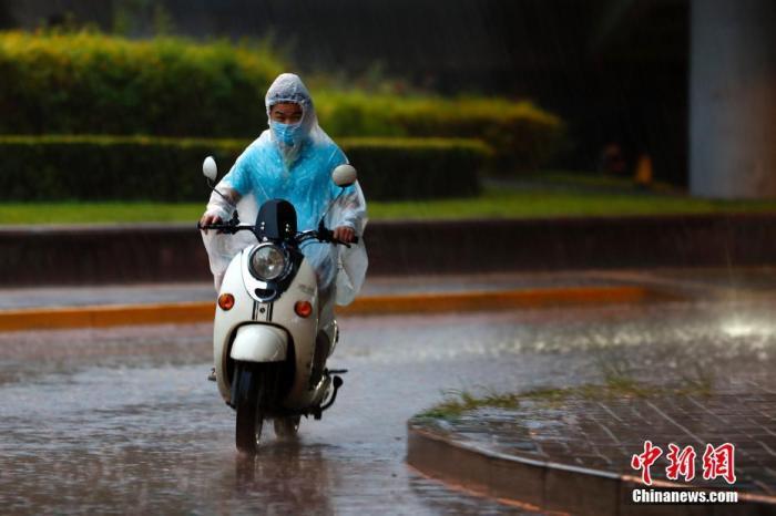 资料图:市民在雨中骑行。 中新社记者 富田 摄