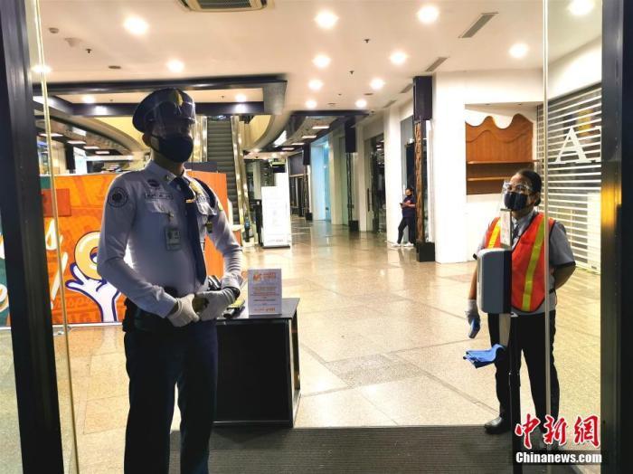 當地時間8月13日,在菲律賓首都馬尼拉CBD馬卡蒂綠帶商圈GREENBELT5商場,保安和負責測量體溫的工作人員佩戴口罩和面罩上崗。