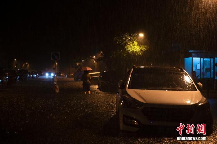 8月12日晚间,北京市迎来强降雨,民众涉水出行。中新网记者 李骏 摄