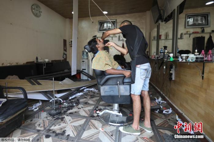 当地时间8月13日,黎巴嫩贝鲁特一家在大爆炸中受损的理发店营业,美发师为顾客刮胡子。黎巴嫩首都贝鲁特港口区8月4日晚发生剧烈爆炸,造成数千人死伤。爆炸还造成约30万民众无家可归。