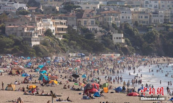 当地时间8月15日,美国旧金山市民在金门大桥附近的贝克海滩纳凉。当日,美国加州的持续高温天气进入第二天,部分地区刷新多年来的最高温纪录。随着轮流断电的继续进行,加州正面临近20年来最严重的电力中断。 中新社记者 刘关关 摄