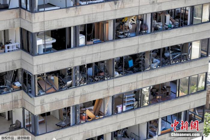 當地時間2020年8月16日,黎巴嫩首都貝魯特,挖掘機在貝魯特港口的爆炸現場進行拆除工作。圖為港口附近被爆炸摧毀的建筑。