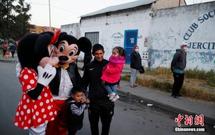 """当地时间8月16日,阿根廷疫情期间,实行封锁措施,布宜诺斯艾利斯Fuerte Apache街头,卡通人物上街送抱抱,""""米奇""""和""""米妮""""与行人合影。"""