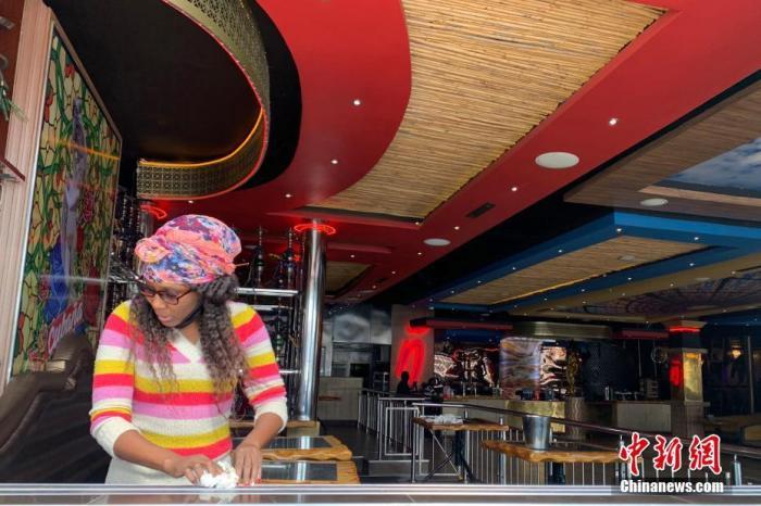 """当地时间8月18日,南非约翰内斯堡一知名酒吧店员正在为重新营业做准备。随着南非新冠肺炎疫情好转,从8月17日起,南非针对疫情的""""封锁令""""从三级降为二级。 <a target='_blank' href='http://www.chinanews.com/'>中新社</a>记者 王曦 摄"""