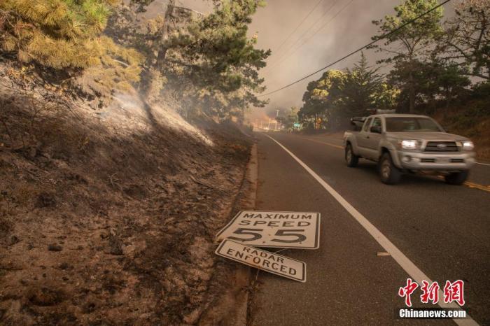 圣马特奥县和圣克鲁斯县交界山区的一场大火正迅速蔓延,汽车驶过一块倒塌的限速牌。/p中新社记者 刘关关 摄
